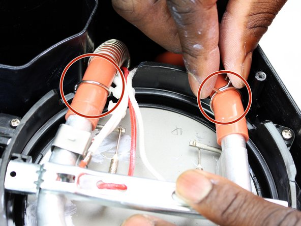 Squeeze the two hose clamps together as you slide the clamps away from the heating element.