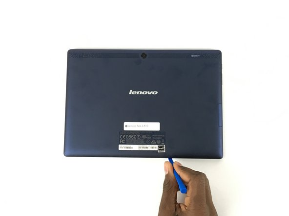 Image 1/2: Use a plastic opening tool to pry open the back cover of the tablet.