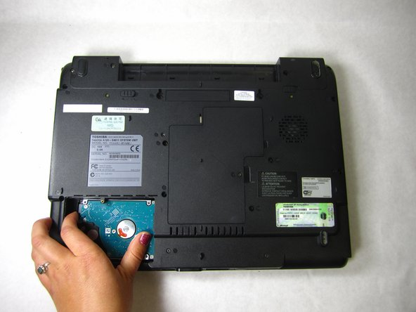 Remove the hard disk by gently applying pressure with your thumb while sliding the hard disk to the left.