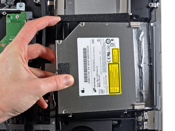 Image 1/1: Carefully pull the optical drive off its mounting pins on the edge of the outer case to gain clearance for disconnecting the optical drive cable.