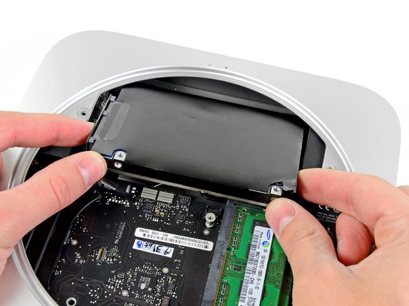 Image 2/2: Pull the hard drive away from the front edge of the mini and remove it from the outer case.