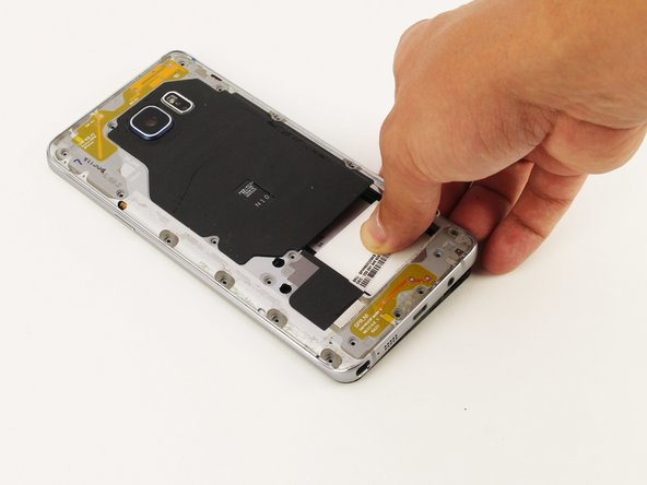 Grip the back of the device and press down on the white square to remove the middle housing.