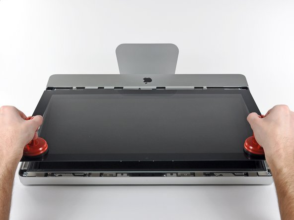 Image 2/2: Pull the glass panel away from the lower edge of the iMac and carefully set it aside.