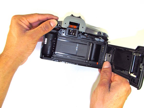 Image 1/2: Buttons may slip out of the camera's top as the top is pulled off the camera (shown in picture two).