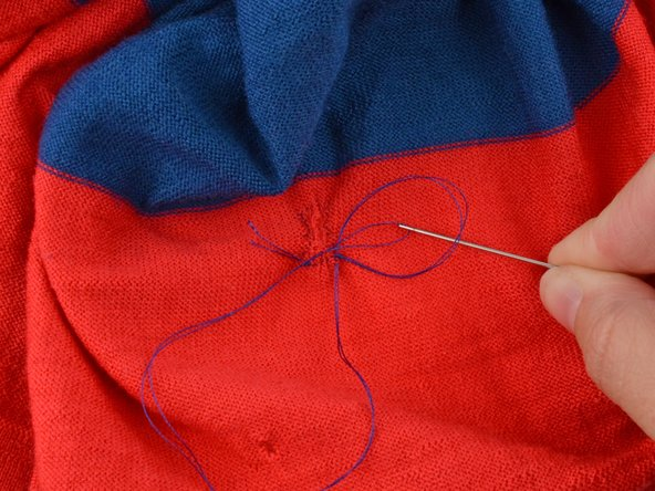 Pull the needle through the loop creating a knot.