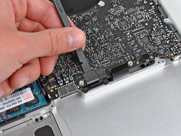 Use the flat end of a spudger to pry the trackpad cable connector up out of its socket on the logic board.