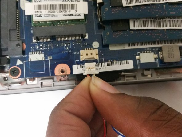 Using your fingers, remove the speaker connector from its port by sliding it out.