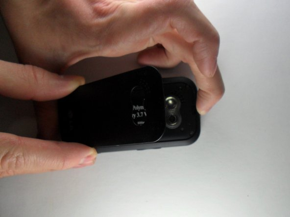 Remove the back cover of the phone by pushing the rectangular button located on the back top-side of the phone.