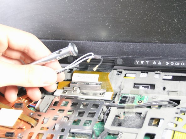 Using the Phillips #0 Screwdriver, lift the metal fastener up and remove the black and white wires.