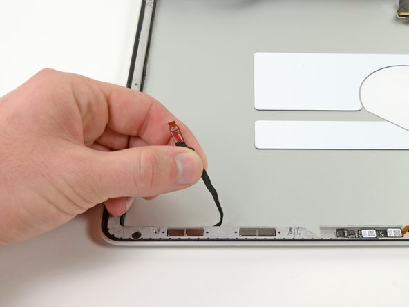 Image 1/2: Continue de-routing the AirPort/iSight cable from the right side of the display assembly.