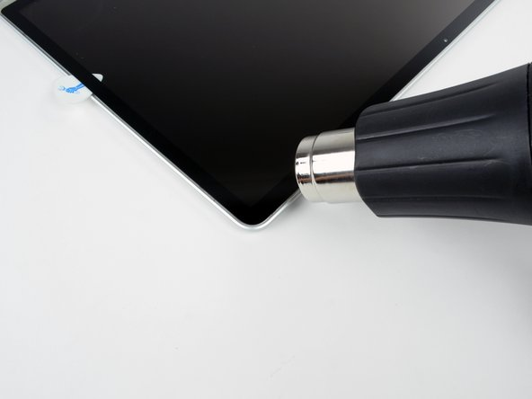 Image 1/3: Use a heat gun to soften the adhesive under the display glass along the right and top edges of the display.