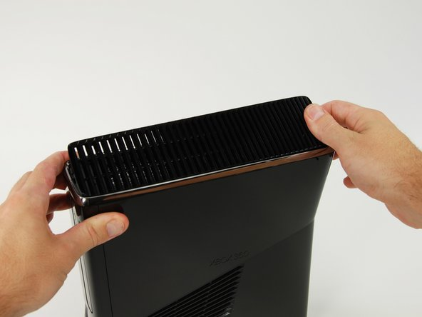 Lift the fan vent up from the freed left side to disengage the clips along the right side.