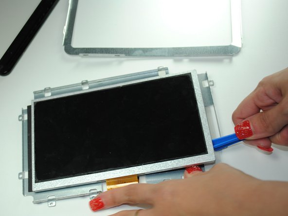 Remove the plastic over the screen and use a spudger or plastic opening tool to remove the screen from the sticky adhesive.