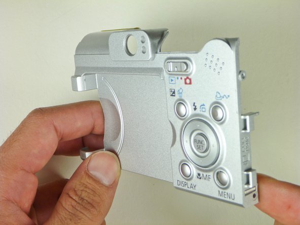 Image 1/2: Flip the casing over and push on the back of the broken button with either your finger or a blunt object until it realigns into its slot.