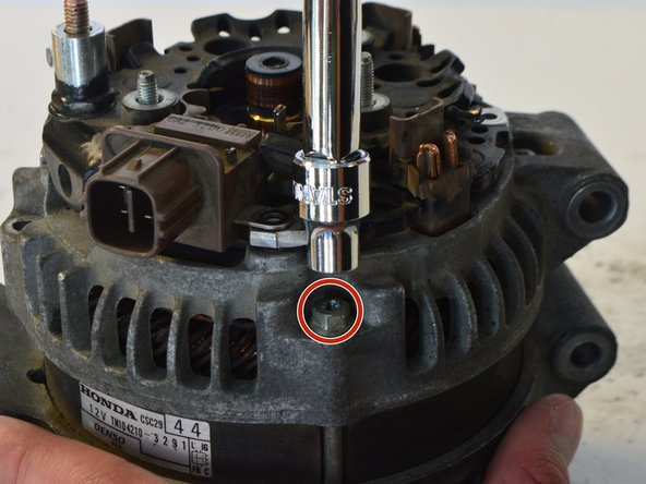 Use a Philips #2 Screwdriver or a 7.5mm socket driver to unscrew the 4, 7.5mm bolts running along the outer perimeter of the alternator