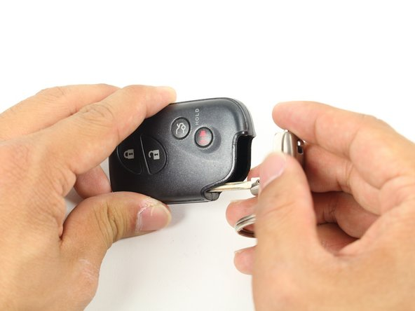 With the button side facing you, pull the metal latch down towards you to pull out the key.