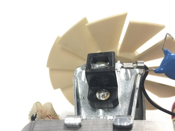 Using a little pressure, insert a 02 Phillips screw driver into the little black slot next to where you desoldered the capacitor.  Use this to hold down the clip that keeps it in place.