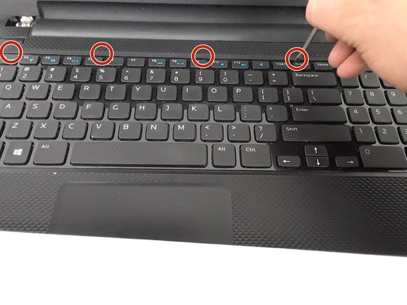 Use a small screwdriver to press in the keyboard latches.