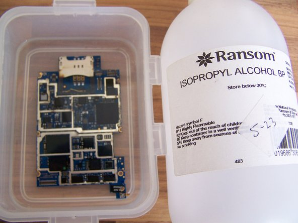 Submerge the logic board in isopropyl alcohol, and allow it to soak long enough to loosen hardened residue, and to displace any remaining water or other liquid. Use a soft brush to remove visible corrosion and residue.