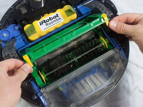 Pinch the yellow tabs on the sides of the brush cage and lift up to open.