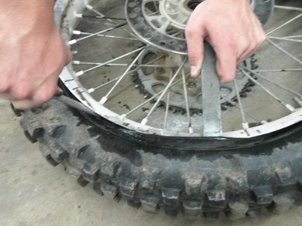 Then take the dirt bike tire iron and wedge it between the rim and tire. Once wedged use leverage from the rim to pull the tire up and away.