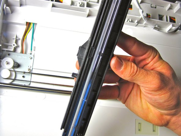Remove the black component by gently pulling it up from the black scanner belt