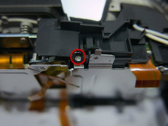 Photo 1: Remove 4 mm screw holding the plastic plate above the flash batteries