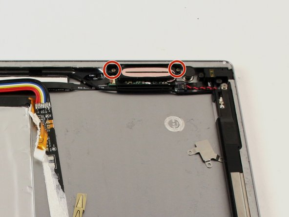Locate and remove the two 2.5mm Phillips #000 screws on either side of the wire coil.
