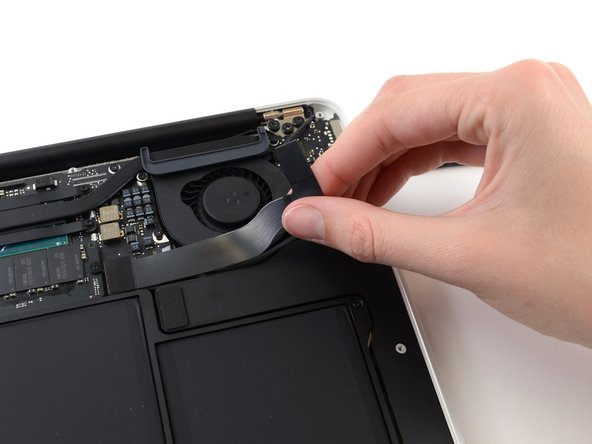 Carefully peel the I/O board cable from the adhesive securing it to the top of the fan.