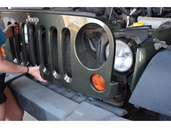 Firmly pull the bottom of the grill until the grill disconnects from the jeep.