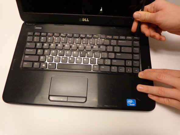Using the spudger, push the tabs away from the keyboard and pull the keyboard up away from the laptop.