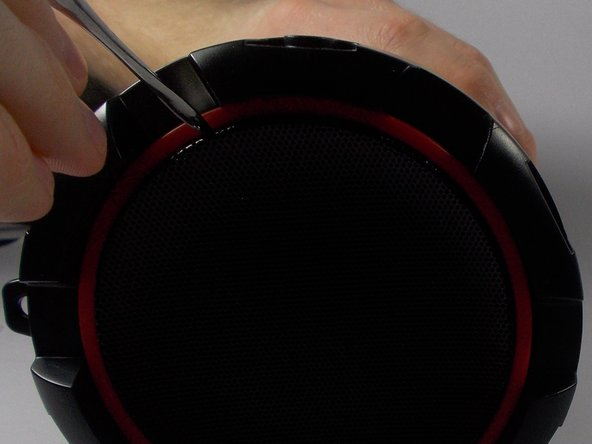 Use a metal spudger to remove the mesh speaker cover by wedging the narrow end into the center of the outer edge of the mesh touching the red plate.