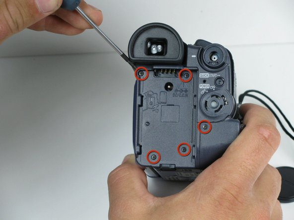 Rotate the camcorder so that the eye piece is facing you, and remove the battery. Remove the four black 4.5mm screws, which sit behind the battery. Then, remove the 5th screw to the right of the battery dock.
