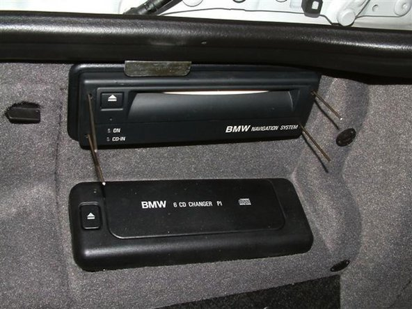 "Image 1/3: In the back of the car locate the navigation computer drive and insert 4 pieces of a cutup coat hanger or a ""Radio Removal Tool"" into the holes of the drive"