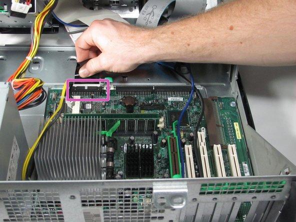 Desconecte el cable plano de la unidad de disco flexible tirando suavemente de la lengüeta negra alejándola de la placa base.