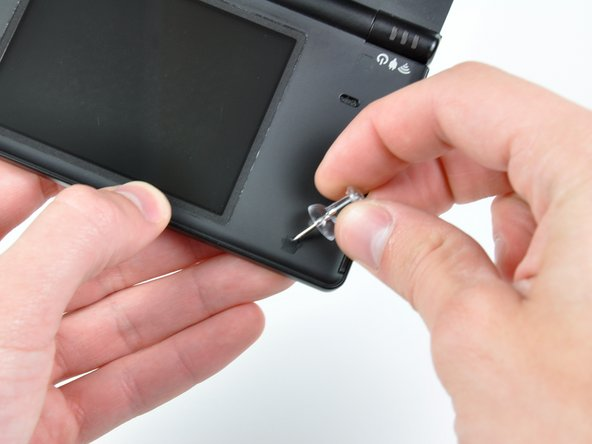 Use a pushpin to remove the four plastic screw covers (highlighted in red) on the front bezel.