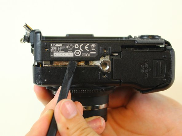 Using a spudger, carefully pry open the back side of the camera starting directly under the camera's serial label.