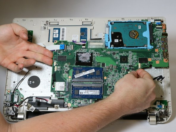 Once all connectors are separated from the motherboard and the USB port area is freed, carefully lift on either side of the motherboard to remove it.