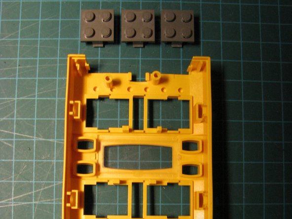 Image 2/2: Squeeze the clips at the top and bottom of each Lego 9V connector. Push them through.