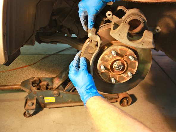 Pull the two old brake pads out of both the front and rear of the pad bracket.