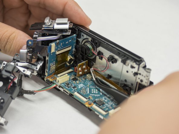 Image 2/2: With your tweezers in your right hand, gently remove the wire connecting the speaker to the motherboard.