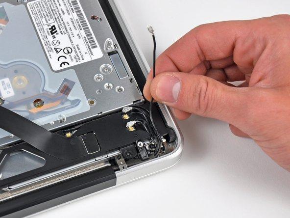 Dégagez les trois câbles d'antenne de leur canal sur le boîtier AirPort/Bluetooth.