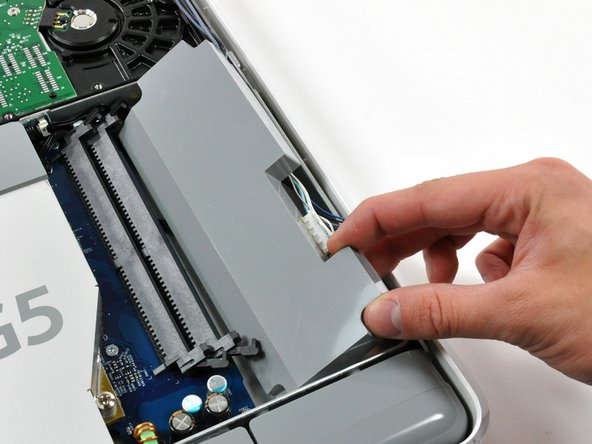 Slide the inverter toward the edge of the mid-plane, then lift it out of the iMac.