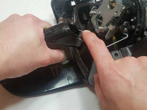 Pull and hold the throttle trigger to expose the attachment point for the trigger-portion of the throttle linkage