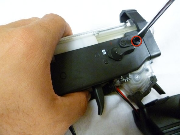 Using a flathead screwdriver, remove the two 5mm screws beside the safety switch on both sides of the gun.