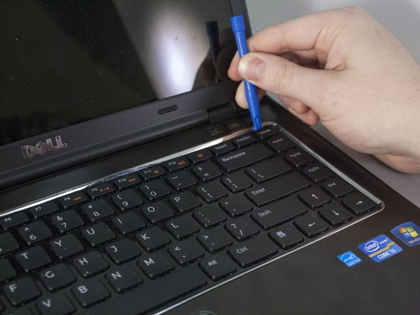 Using a plastic opening tool, pry up on the four tabs holding the keyboard in place. Be careful not to damage the keys on the top of the keyboard. You will know when it has been successfully pried open when you hear four clicks from the top of keyboard.
