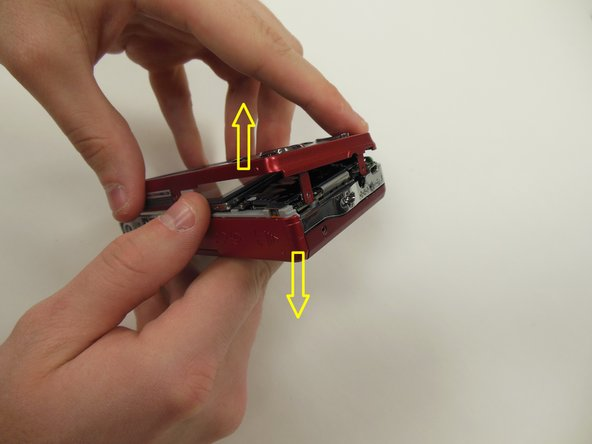 After screws are removed, using both hands, carefully pull the frame apart from the camera as indicated.