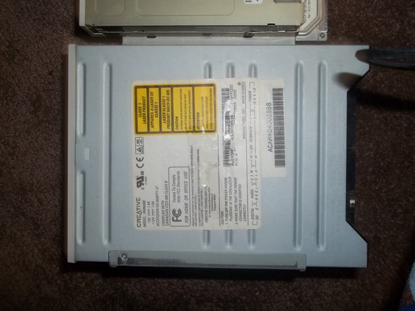 Slide the optical drive forward and lift it up from the right side, the side closest to the floppy drive.