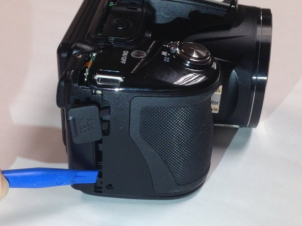 Insert a plastic opening tool between the back and front surface components of the camera.