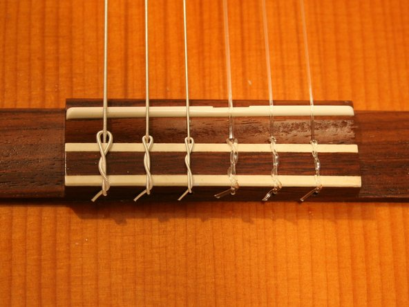Do not completely remove the loose ends. Cutting the end too close to the tuning peg or the bridge may cause the string to slip out of position later. Leave at least a half inch piece in place.